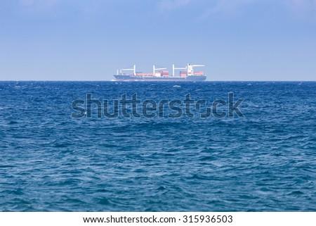 freight ship on the horizon of the sea - stock photo