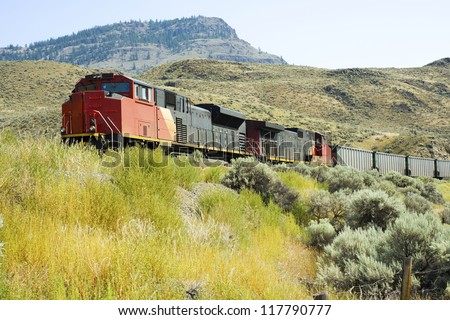 Freight Train - A freight train passes through the hillside of Kamloops, British Columbia, Canada - stock photo