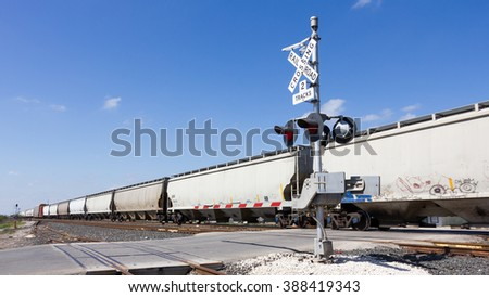 freight train speeding through a crossing at full speed - stock photo