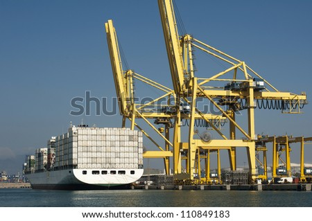 Freighter in port being loaded with containers.Cranes in port - stock photo
