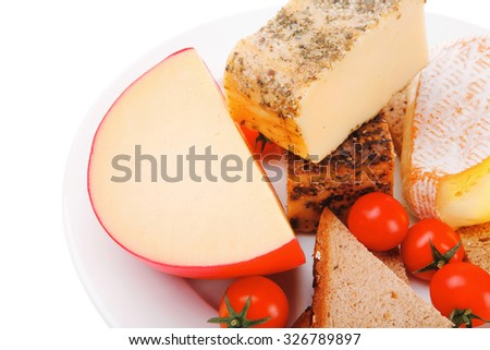 french aged cheeses on dish with bread and tomatoes - stock photo