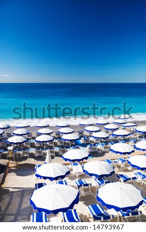 French beach with umbrellas. Nice France. - stock photo