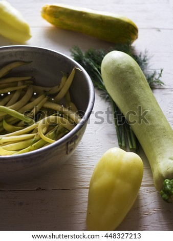 French bean in a colander, zucchini, bell pepper and dill on a white painted wooden surface - stock photo