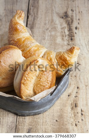 french breakfast buns bread roll and croissant on vintage tray and wood - stock photo