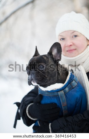 French bulldog in the arms of a woman in winter - stock photo
