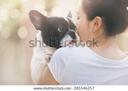 French bulldog is cute kissing girl. She carry on a dog. - stock photo