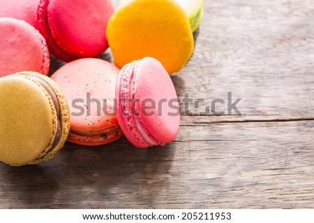 French colorful macarons on wood table - stock photo