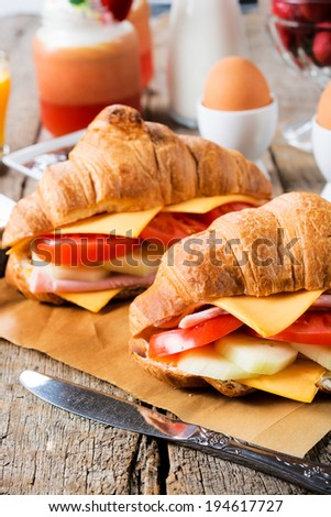 French croissants stuffed with vegetables,cheese and ham.Selective focus on the front sandwich - stock photo