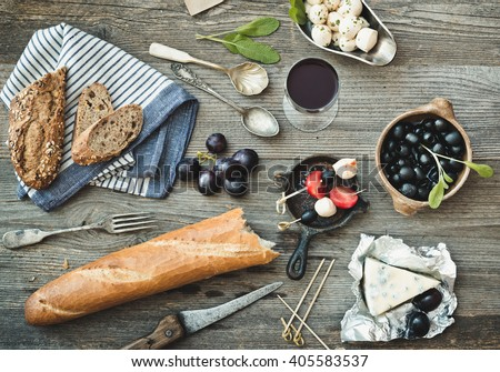 French cuisine. Different types of cheese, wine and other ingredients on a wooden table - stock photo