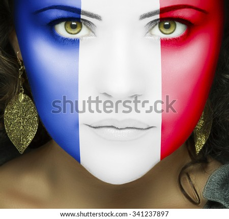 French flag on face of woman with green eyes - stock photo
