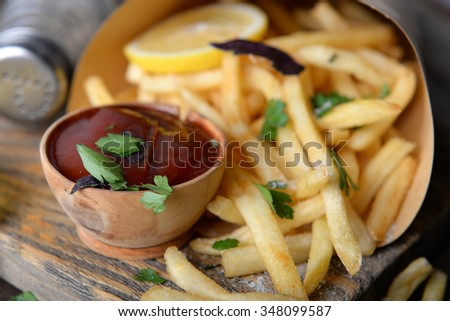 French fried potatoes in craft paper on cutting board - stock photo
