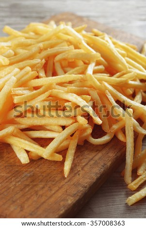 French fried potatoes on cutting board - stock photo