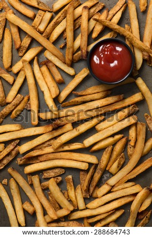 french fries and ketchup in a baking pan, top view, close up, vertical - stock photo