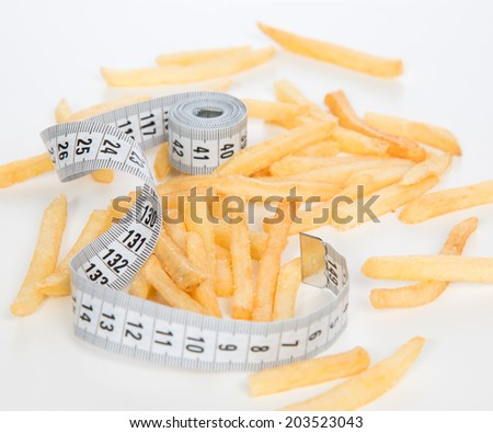 French fries chips meal with tape measure on white background. Healthy weight loss diet concept. - stock photo
