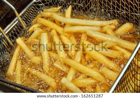 French fries in a deep fryer closeup - stock photo