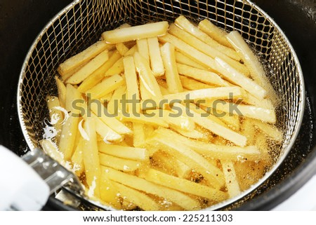 French fries in deep fryer, closeup - stock photo