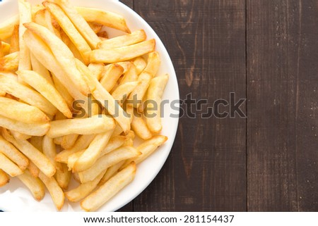French fries on white dish on wooden background. - stock photo