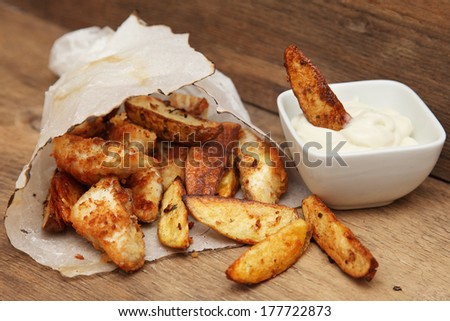 French fries potato wedges in recycled kraft paper bag on wooden old background. Fast food. Closeup. - stock photo
