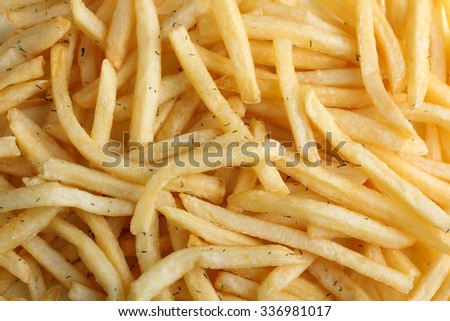 French fries sprinkled with dill on a napkin in a basket with ketchup salt and dill on wooden background closeup - stock photo