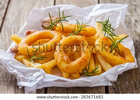 french fries with calamari and rosemary on white paper - stock photo
