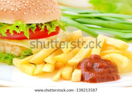 French fries with ketchup and hamburger - stock photo