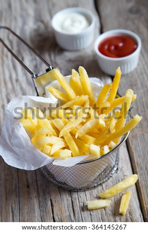 French fries with ketchup and mayonnaise  - stock photo