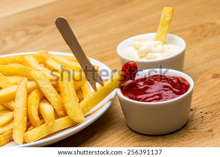 French fries with ketchup and mayonnaise and fork - stock photo