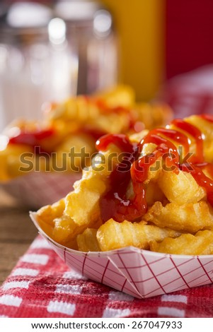 French fries with ketchup on a red and white checkered table cloth and salt and pepper shakers in background - stock photo