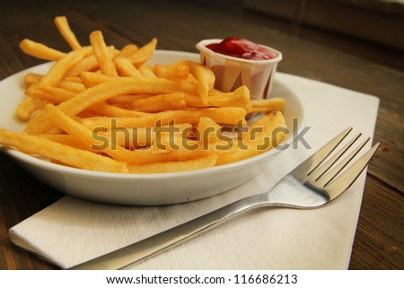 French fries with salt and ketchup in a plate with fork on white napkins - stock photo