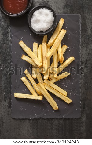 French fries with sea salt and ketchup, on black slate.  Overhead view. - stock photo