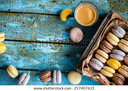 French homemade macarons in a wooden box with coffee, selective focus, space for text - stock photo
