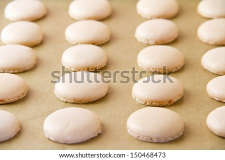 French macaron shells (pronounced macaroon, a popular buttercream filled meringue type cookie or biscuit) on baking sheet lined with baking parchment paper. - stock photo