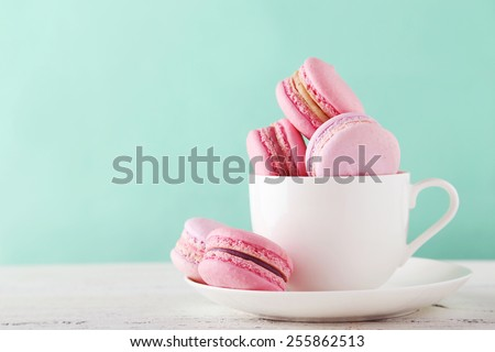 French macarons in cup on white wooden background.Toned image  - stock photo