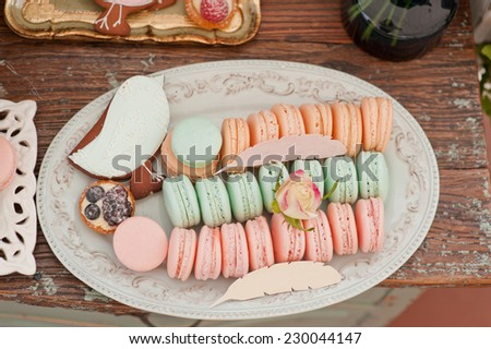 French macaroons and Gingerbread bird on a stand . Candy bar on wedding. - stock photo