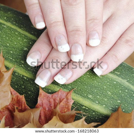 French manicure autumn in the goodies background - stock photo