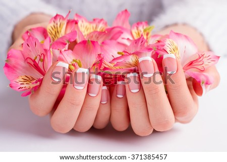 French manicure closeup. Delicate freesia in female hands. - stock photo