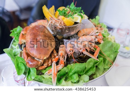 French Mixed Cold Seafood platter with Lime, Ice and parsley on vegetable and seaweed in line buffet for party in Paris, France. Selective Focus - stock photo