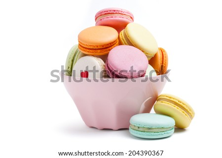 French multicolored macaroon cookies in deep pink plate on a white background isolated - stock photo
