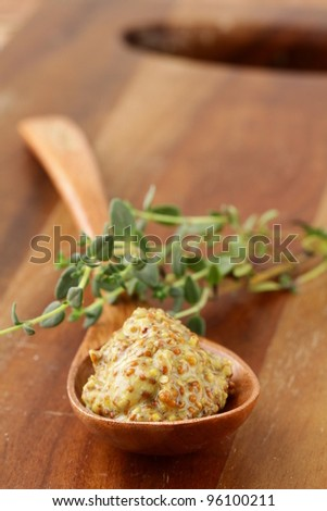 French mustard sauce in a wooden spoon - stock photo