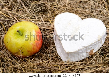 French Neufchatel cheese heart-shaped, with an apple on straw - stock ...