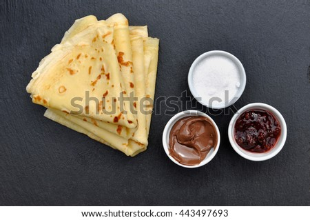 french pancake with pots of sugar, jam and chocolate on dark background - stock photo