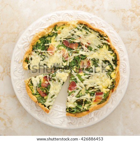 French quiche pie with egg, cheese and spinach on the plate. Top view - stock photo