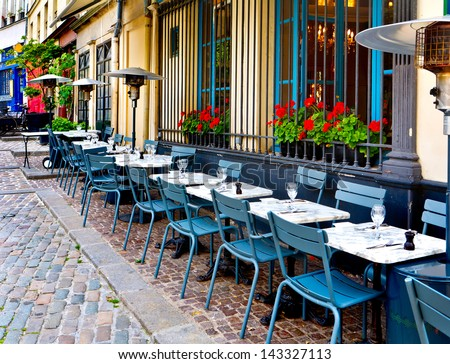 french restaurant - tables and chairs on the street - Paris, France - stock photo