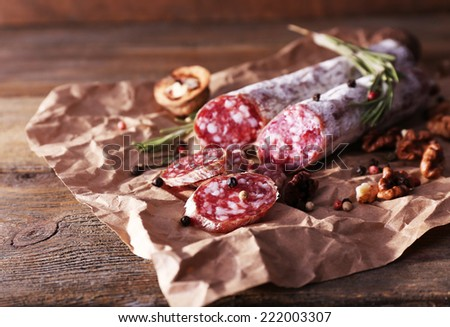 French salami and walnuts on craft paper on wooden background - stock photo