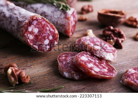 French salami and walnuts on wooden background - stock photo