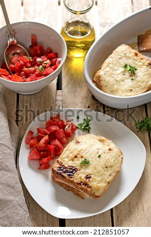 French sandwiches Croque-Monsieur with bechamel sauce, tomato salad and prosciutto ham. Selective focus - stock photo