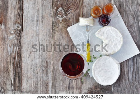 French soft cheese with a different jam and a glass of red wine on the natural wood backgraund - stock photo