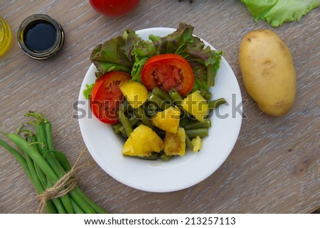 French string bean salad in white dishes on the wooden surface. Top view - stock photo