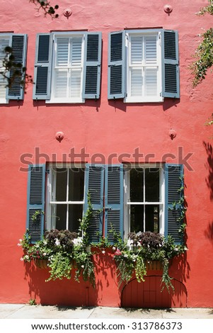 French style black shutters with flower boxes and a stucco wall in Charleston South Carolina - stock photo