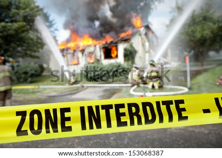 "French ""Zone Interdite"" tape with firefighters and a burning house in the background - stock photo"